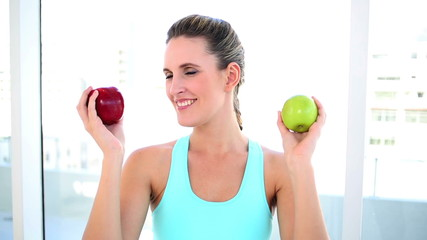 Smiling fit woman showing two apples