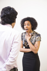 young ethnic business woman looks shocked while talking to man