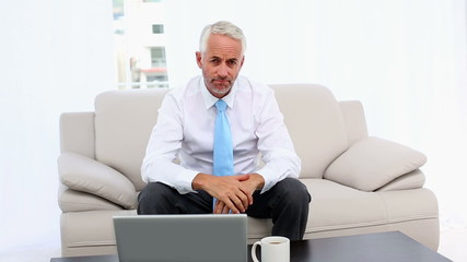 Stressed businessman looking at laptop then camera