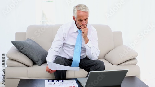 Businessman working on the couch and smiling at camera