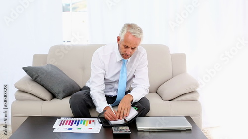 Businessman writing in his diary and smiling at camera