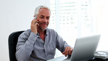 Casual businessman working on laptop and talking on phone