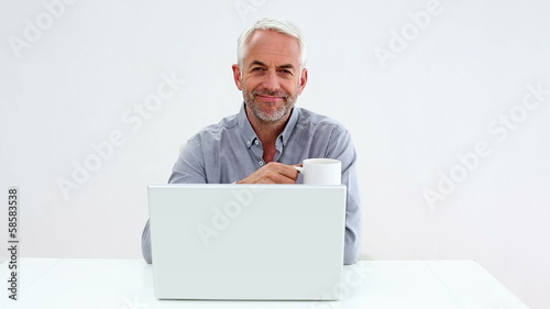 Casual businessman working on laptop and drinking coffee