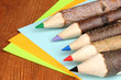 Colorful wooden pencils with sheets of paper on wooden table