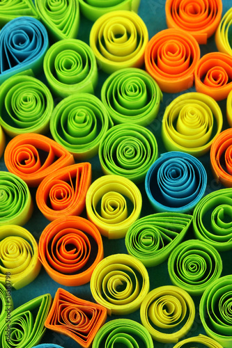 Colorful quilling on blue background close-up