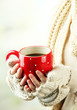 Female hands with hot drink, on light background