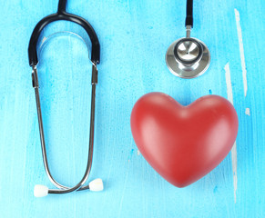 Stethoscope and heart on wooden table close-up