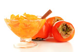 Ripe persimmons with jam in glass saucer and cinnamon isolated