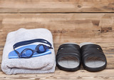 glasses for swimming and towel on wooden background