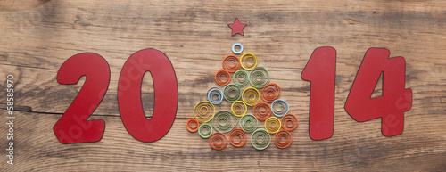 word 2014 and curling paper Christmas tree on wood background
