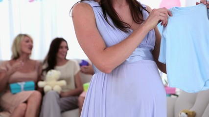 Woman giving pregnant friend a baby gro