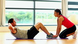 Cute fit man doing sit-ups in fitness hall