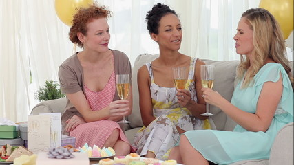 Friends having white wine and chatting at a party