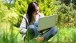 Happy young woman sitting on grass using laptop