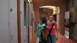 Two students walking down hallway to locker