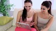 Pretty smiling friends chatting on the couch using tablet pc