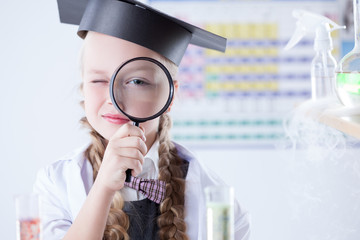 Smiling schoolgirl looks through magnifying glass
