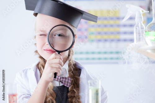 Smiling schoolgirl looks through magnifying glass