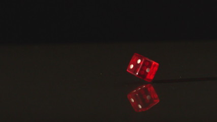 Red dice spinning on black background