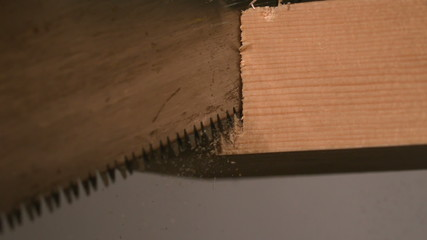 Saw cutting through wood close up