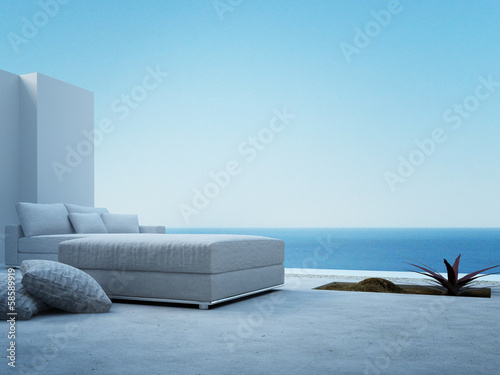 White couch standing on a patio with seascape view