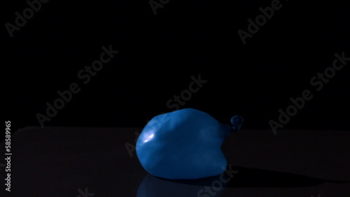 Blue water balloon falling on black background