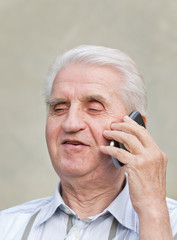 Senior man talks on cell phone and smiles