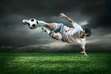 Fototapety Football player with ball in action under rain outdoors