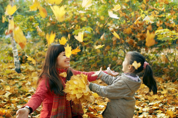 Young happy mother and her daughter play in autumn park