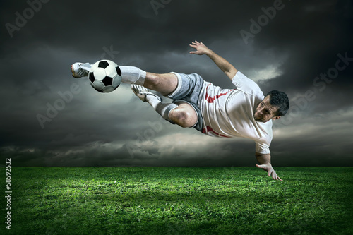 Football player with ball in action under rain outdoors - 58592532