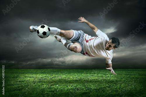 gracz-futbolu-z-pilka-w-akci-pod-deszczem-out