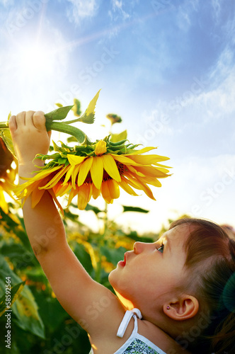 Beautiful little girl and sunflower