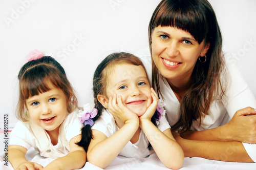 Happy mother and two daughters are on the floor
