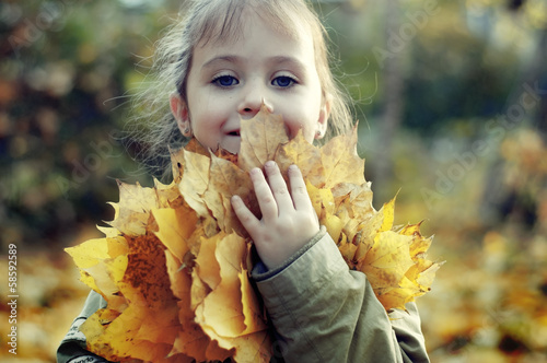 The little lovely girl with autumn leaves
