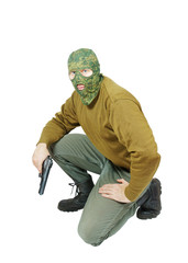 Man wearing camouflage mask with a pistol