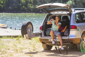 Woman preparing fishing rod at back of car lakeside