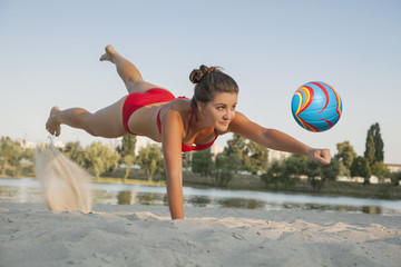 Young beautiful lady is playing volleyball on the beach