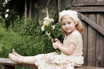 little girl with flowers on wooden bench