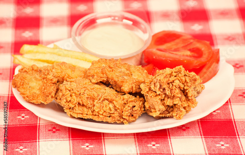 Crispy chicken with white sauce, tomatoes and fries