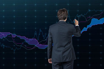 Businessman drawing a stock market graph.