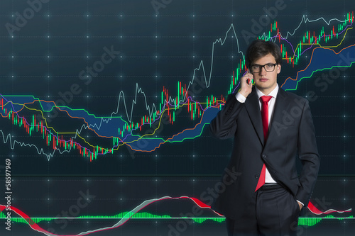 Businessman talking on phone (stock market graph background)