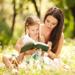 Mother with daughter read the book in the park