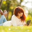 Young pretty woman with tablet in the park