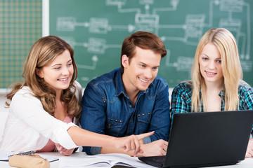 schülerin zeigt mitschülern etwas am laptop