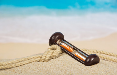 Hourglasses and rope on the sandy coast