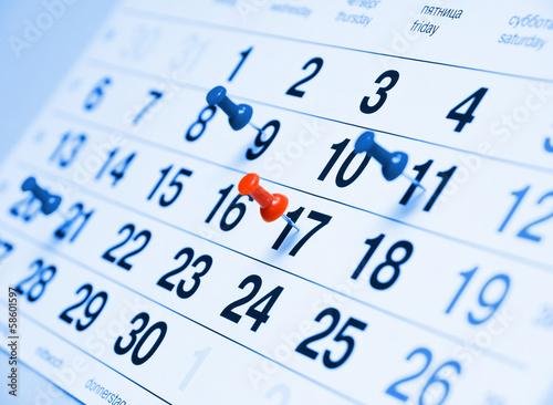 Leinwanddruck Bild Closeup a blue toned calendar page with drawing-pins