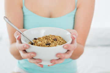 Mid section of a female with a bowl of cereal in bed