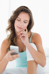 Smiling woman looking at mobile phone in bed