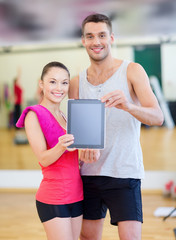 two smiling people showing blank tablet pc screen