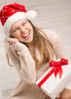 Laughing Santa woman with gift box looking at white snowflakes